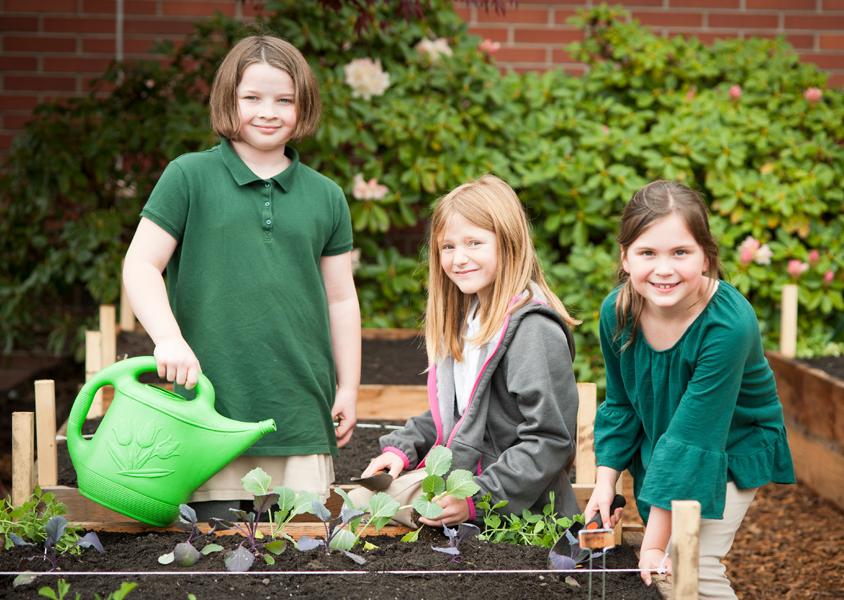 Lower School girls gardening