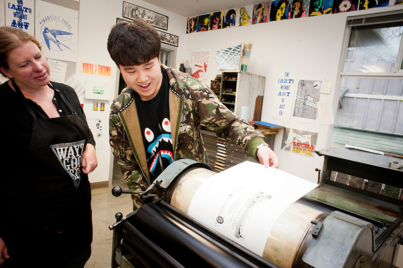 upper school student and teacher work on the printing press