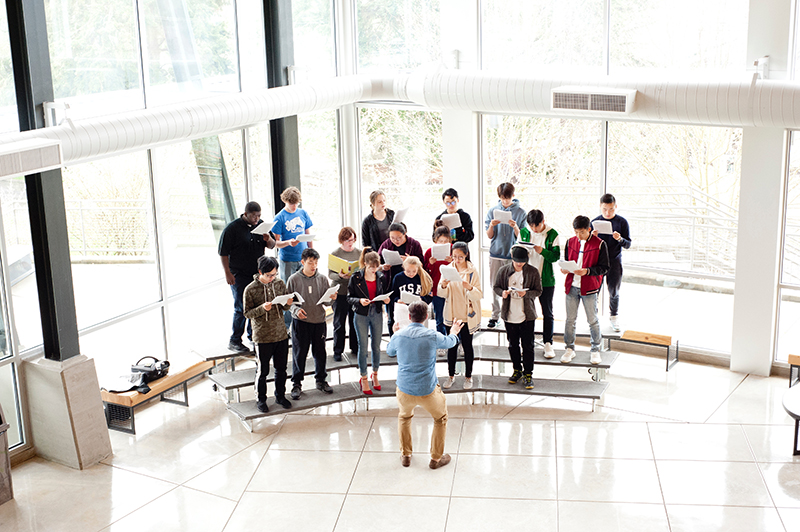 upper school chorus rehearses in brightly lit lobby of language and performing arts center