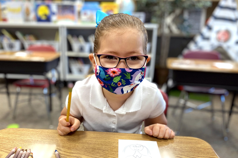 lower school student working at her desk in a mask