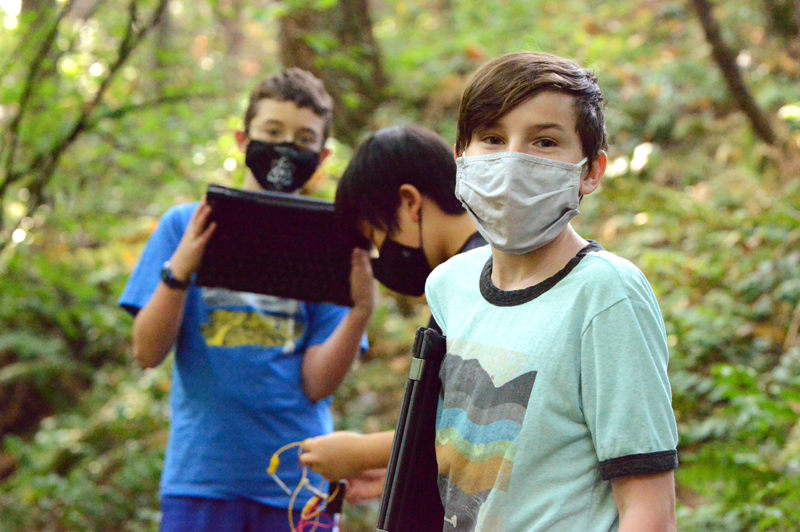 Middle School science students in masks in the CWA woods