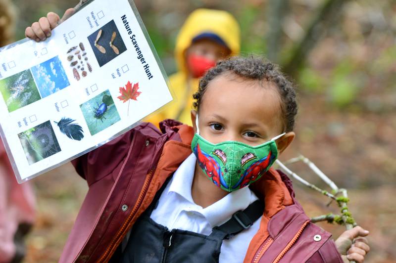 Preschool student in the woods wearing a mask on the CWA trails.